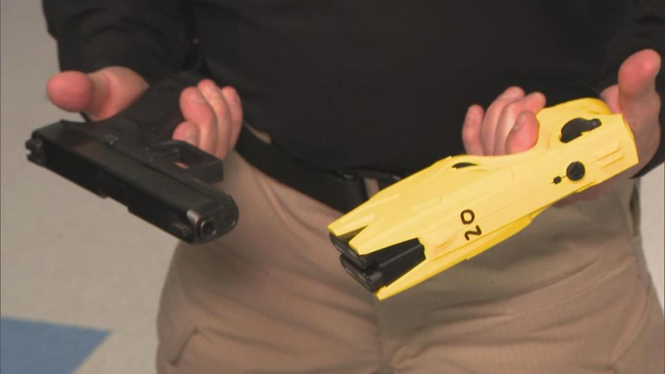 A man holding a handgun and a taser